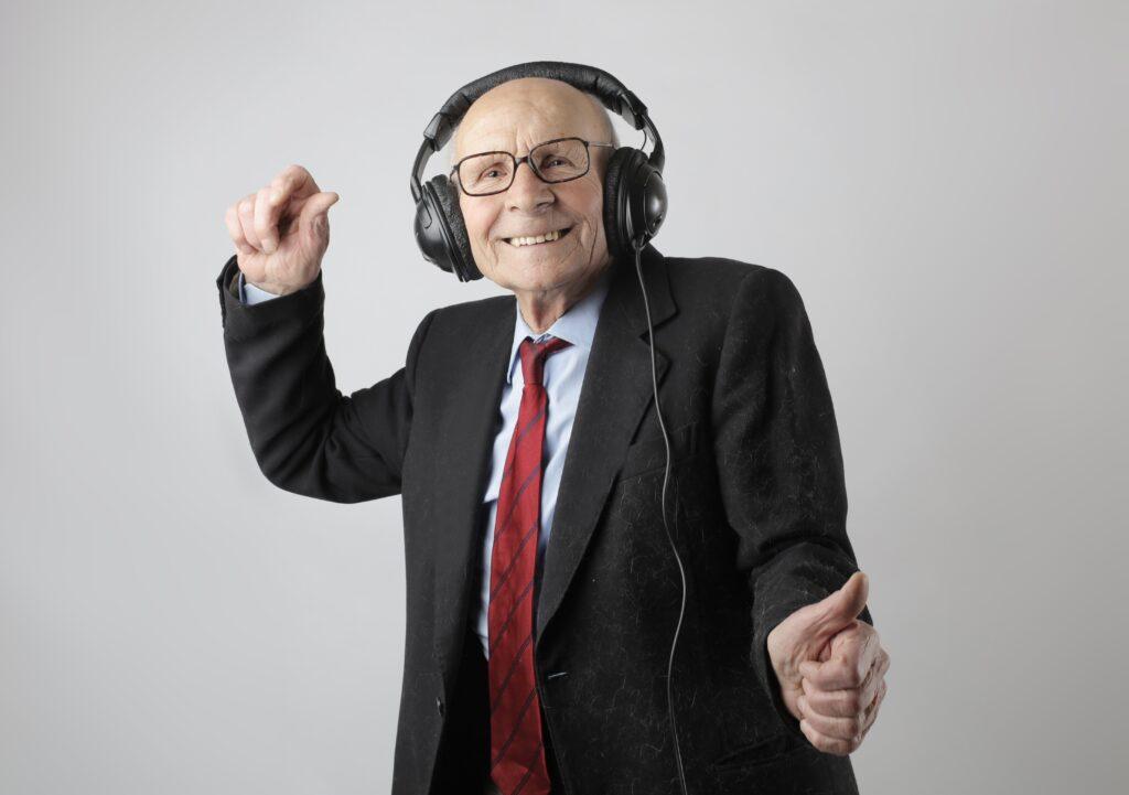 Elder man wearing headphones with coat and tie