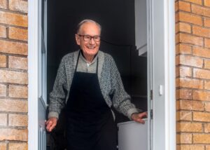 Old man with eyeglass and afron smiling